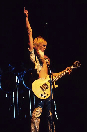 """Ronson5    <strong></noscript>The Concert Tapes:</strong><br /> This is the famous concert in which Bowiee descended on the stage in a cage hanging 17 meters above the stage. A spectacular opening of this concert which was given on Valentine's Day and was also the first concert of the short US Tour II. It was a full house. The group <strong>Fumble</strong> was to do the first part of the programme,but for some reason it was cancelled.</p> <p><em>""""They can't see,sit down!""""</em> some one cries out after <strong>Hang on to Yourself</strong>. After <strong>Ziggy Stardust</strong> Bowie says: <em>""""It's nice to come down to New York again""""</em>.<br /> Although the band was reinforced with additional saxophone players,Bowie did the sax solo in <strong>Soul Love</strong> himself. This tape and that of the second evening in NY are the only 1973 tapes which include this number.</p> <p>After My Death a screen was raised at the back of the stage displaying a cartoon in which the cosmos seems to bear down upon the spectators at the speed of light.<br /> This is a very long concert by the way: no fewer than 21 numbers,including all numbers but one of the entire LP Aladdin Sane which at the time had not yet appeared. After <strong>Watch That Man</strong> Bowie says: <em>""""In case you'd like to know,we've made a new album,that was the first,it's called <strong>Watch That Man</strong>. As you might know,we brought some new people with us tonight,a very quick one is Ken Fordham who's very quick but a little bit tired,Geoffrey and Hutch and you may know Mike Garson from my last tour. This is a track from the new album anyway,this one is called <strong>Drive in Saturday</strong> which was written between Phoenix and Seattle""""</em>.<br /> The audience respond well to the new numbers but when <strong>Cracked Actor</strong> is over no one applauds,probably because the audience are not sure whether it is really over or may yet go on. <em>""""That was called <strong>Cracked Actor</strong>""""</em> """